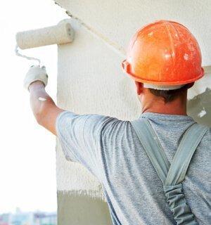 Handwerker streicht Fassade