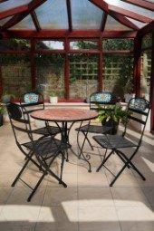 Wintergarten mit einem Tisch und Stühlen
